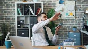 Langzame motie van gelukkige miljonair die geld werpen die in bureau lachen stock videobeelden