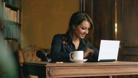 Langzame motie van glimlachend studentenmeisje die aan laptop in universitaire bibliotheek binnen werken stock videobeelden