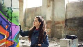 Langzame motie van graffitikunstenaar het schilderen op muur in de verlaten bouw die de verf van de aërosolnevel gebruiken Aantre stock videobeelden