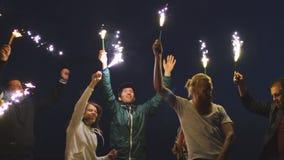Langzame motie van Groep jonge vrienden die een strandpartij hebben Vrienden die en met sterretjes in schemering dansen vieren stock videobeelden