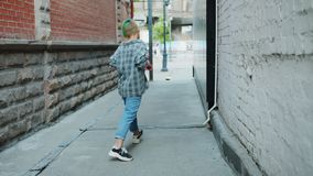 Langzame motie van het Aziatische tiener genieten die in stadsstraat het glimlachen met een skateboard rijden stock footage