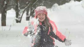 Langzame motie van het blije kind spelen in sneeuw Gelukkig meisje die pret buiten de winterdag hebben stock footage