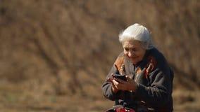 Langzame motie van het gelukkige oude vrouw glimlachen die het scherm van smartphone bekijken Portret van een gelukkige bejaarde stock video