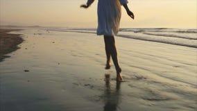 Langzame motie van het gelukkige vrouw lopen op natte kust tijdens zonsondergang stock videobeelden