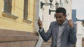 Langzame motie van het Gemengde raszakenman spreken bij smartphone en gelukkig dansen over in openlucht het maken van overeenkoms stock footage