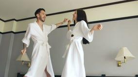 Langzame motie van jong gelukkig paar in badjassprong en dans op bed in hotel tijdens hun wittebroodswekenvakantie stock footage