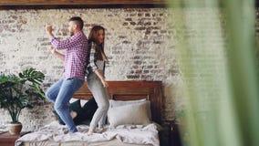 Langzame motie van jong mooi en houdend van paar die hebbend pret en thuis lachend in bed dansen Achteloosheid, vrije tijd stock video