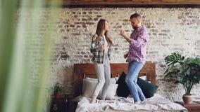 Langzame motie van jong mooi en houdend van paar die hebbend pret en thuis lachend in bed dansen Achteloosheid, vrije tijd stock footage