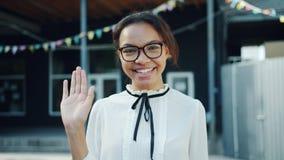 Langzame motie van jonge Afrikaanse Amerikaanse studenten golvende hand die in openlucht glimlachen stock footage