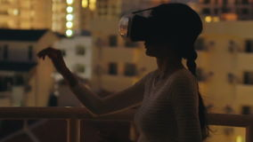 Langzame motie van jonge vrouw op dakterras gebruikend virtuele werkelijkheidshoofdtelefoon en hebbend VR-ervaring bij nacht stock footage