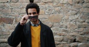 Langzame motie van knappe Afrikaanse Amerikaanse kerel die zonnebril in openlucht opstijgen stock footage