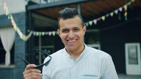 Langzame motie van knappe jonge Arabier die zonnebril opstijgen die in openlucht glimlachen stock footage