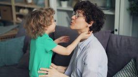 Langzame motie van leuke kind het kussen moeder koesteren en hand die dan thuis lachen stock footage