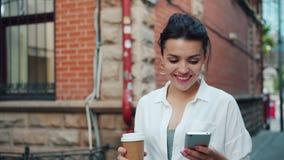 Langzame motie van mooie dame die de koffie van de smartphoneholding het lopen het glimlachen gebruiken stock video
