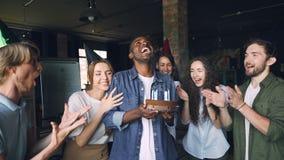 Langzame motie van opgewekte Afrikaanse Amerikaanse mensen blazende kaarsen op verjaardag cake en het lachen terwijl zijn team is stock footage