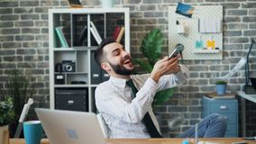 Langzame motie van rijke kerel die dollars werpen die in modern bureau lachen stock video