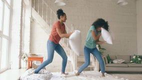 Langzame motie van twee gemengde ras jonge mooie meisjes die thuis op bed en strijdhoofdkussens springen die pret hebben stock videobeelden