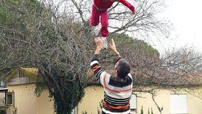 Langzame motie van vader die zijn aanbiddelijke dochter in de lucht werpen stock footage