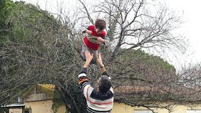 Langzame motie van vader die zijn aanbiddelijke zoon in de lucht werpen stock videobeelden