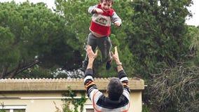 Langzame motie van vader die zijn aanbiddelijke zoon in de lucht werpen stock footage