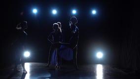 Langzame motie van vier ballerina's het dansen modern ballet over schijnwerpers stock footage