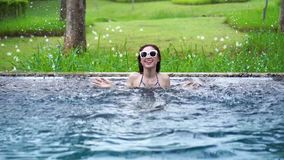 Langzame motie van vrouw in pool en speelwaterplons stock videobeelden