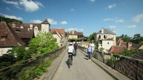 Langzame motie - Vrouw het cirkelen op weg door dorp in Frankrijk stock footage