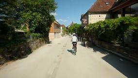 Langzame motie - Vrouw het cirkelen op weg door dorp in Frankrijk stock video