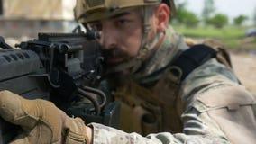 Langzame motieclose-up van een militair en zijn militair kanon tijdens een speciale opleidingsoefening stock videobeelden