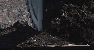 Langzame motielading van een graafwerktuig in mijnbouwvrachtwagen De steenkool van de graafwerktuiglading in grote stortplaatsvra stock video