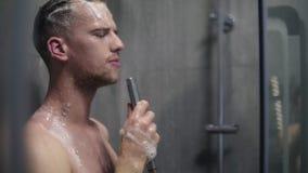 Langzame motielengte van een mens die emotioneel in de douche zingen die het douchehoofd met stromend water in plaats van a gebru stock video