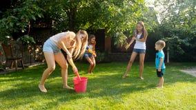 Langzame motielengte van gelukkige vrolijke familie die pret in tuin met waterkanonnen en tuinslang hebben Bespattend water  stock video