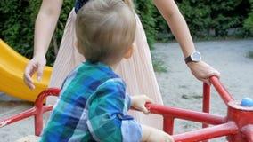 Langzame motielengte van jonge moeder die haar peuterjongen berijden op kleurrijke carrousel bij park stock footage