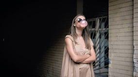 Langzame motielengte van jonge vrouw die grote bel van kauwgom blazen stock footage
