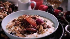 Langzame motiemening: bessen die over een kom yoghurt voor ontbijt met bessen en droge vruchten vallen stock footage