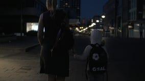 Langzame motiemening van vrouw met zoon het gaan op de nacht lege voetstraat, Rotterdam, Nederland stock footage