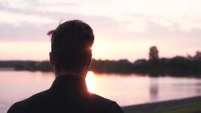 Langzame motiemens opleiding dichtbij zonsondergangrivier Achtermenings mannelijke sportman die bij stil water en bospanorama opw stock video