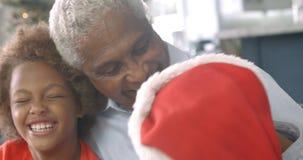 Langzame motieopeenvolging van jongen en meisjeszitting op bank met grootvader in Kerstmistijd stock video