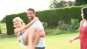 Langzame Motieopeenvolging van Vrienden die Hebbend Pret in Tuin spelen stock footage