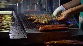 Langzame Motieverkoper die Taiwanese kip op stok kookt De straat van de nachtmarkt stock video