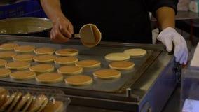 Langzame Motieverkoper het koken dorayaki bij kant van de wegtribunes Azië Aziatische Pannekoek stock videobeelden