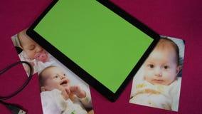 Langzame panning van mooie babyfoto's met het tablet groene scherm FDV stock videobeelden