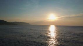 Langzame vlucht boven kleine golven die mooie zonsopgang en bergen op horizon onder ogen zien Luchtdiehommel van mooie ochtend wo stock video
