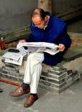 Langzhong, China: Elderly Man Reading Newspaper Royalty Free Stock Photos
