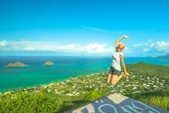 Lanikai Hike Jumping. Hawaiian hiking. Happy woman celebrates one of most picturesque Oahu hiking trails in Hawaii. Joyful carefree hiker jumping during Lanikai Stock Images