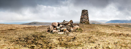 Lank Rigg Summit. An Old trig point ontop of a Cumbrian fell. A rock cairn is in the foreground. The trig points were used to triangulate map references. Many Royalty Free Stock Photos