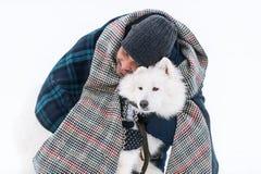 Lankan man för ung sri som omfamnar den fasta vita fluffiga hunden i vinter Arkivbilder