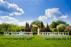 Wedding arch and white chairs on nature background. Lanscape full vertical view of wedding reception for marriage ceremony with flower decoration. White chairs Stock Images
