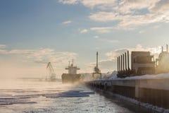 Lanscape industrial do inverno com caminhões e Bulker em um porto, madeira de carregamento Foto de Stock Royalty Free