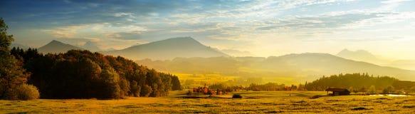 Lansdcape strabiliante della campagna austriaca sul tramonto Cielo drammatico sopra i campi verdi idilliaci delle alpi centrali d Fotografie Stock